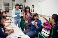 A group of students in discussion in a high school classroom