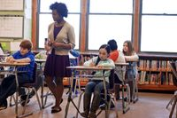 Middle school teacher walking among students writing at their desks
