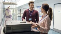 Two adults stand by a copy machine, smiling at each other.