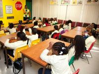 """A group of young students are sitting in a classroom looking towards an adult male. At the front of the class, the wall is yellow. A red and white stop sign is hanging on the wall next to another sign that says, """"yield to pedestrian in crosswalk."""""""