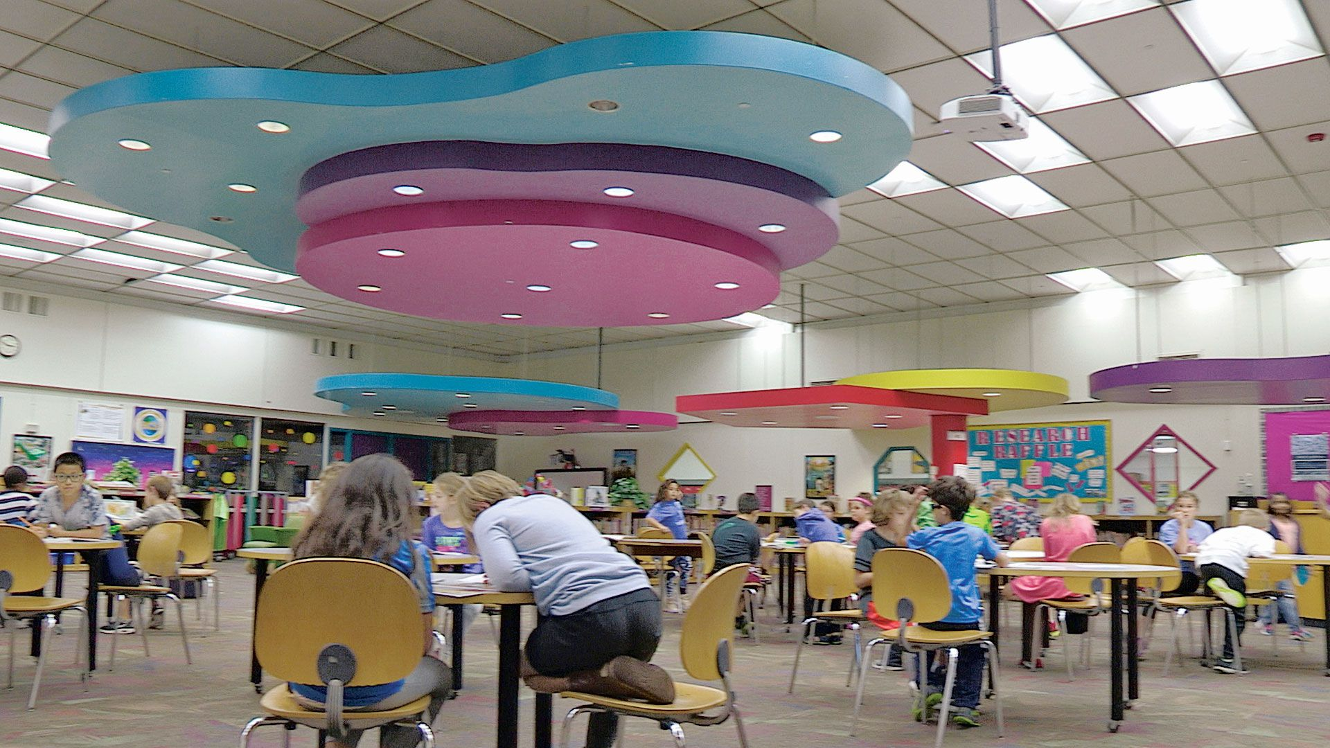 Young students are working at tables in a large multipurpose room with large colorful-shaped decorations hanging from the ceiling.